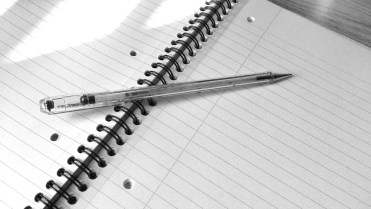 pen and spiral notebook