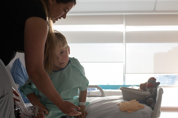 A boy and his nurse in a hospital room.