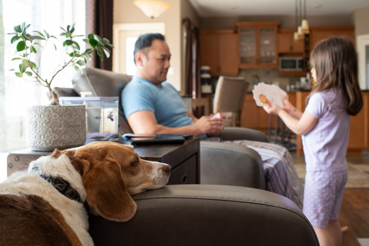 A family plays cards while their dog watches the action.