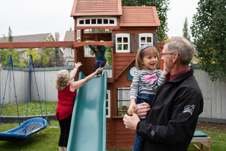 Kids play in their backyard with their grandparents.