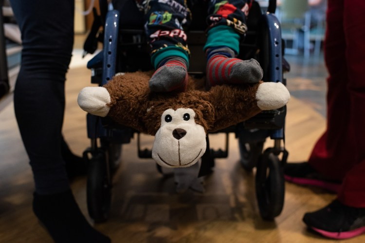 A child sitting in his wheelchair rests his feet on a monkey pillow.