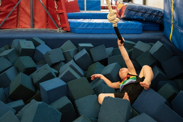 A young boy is laying in a foam pit after swinging on a rope at gymnastics.