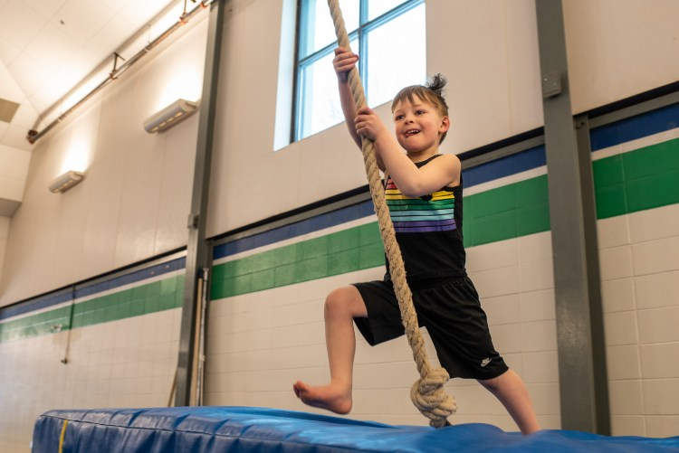 A young boy is preparing to swing on a rope at Canmore Recreation Centre.