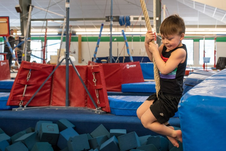 A young boy is getting ready to jump off the rope swing at gymnastics.
