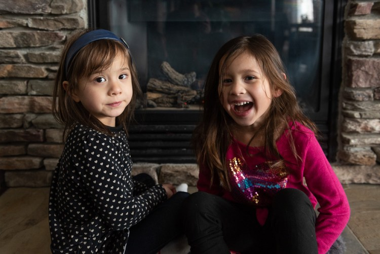 Sisters warming up in front of the fireplace during a documentary family photography session.
