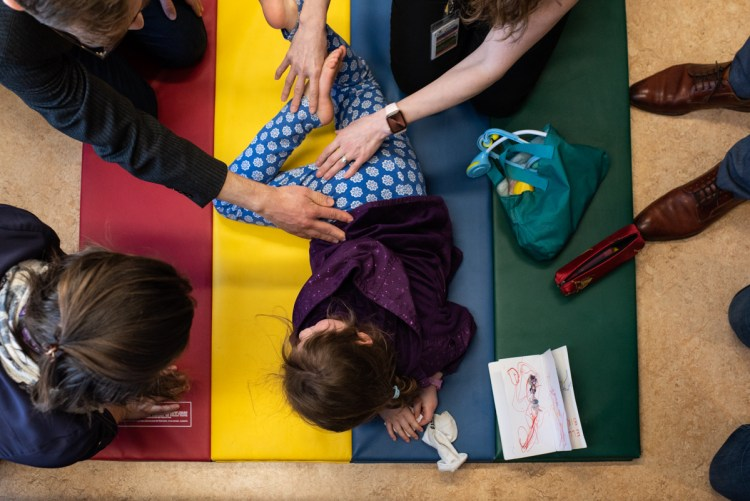 A number of adults are examining a young girl's hip flexibility.