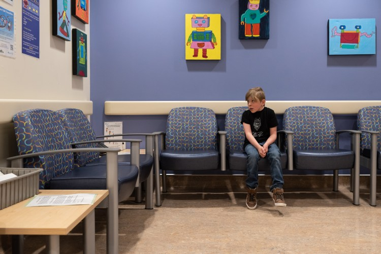 A boy sitting by himself in the cardiology waiting area.