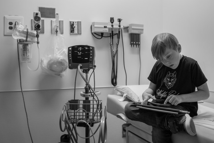 A boy uses an iPad while waiting at a medical appointment.