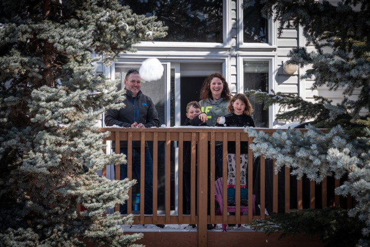 A family throws snowballs from their balcony during the covid-19 pandemic.