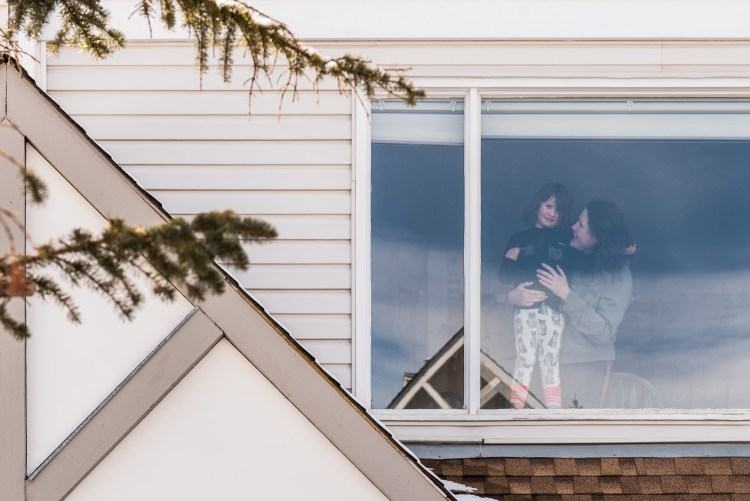 A mother and daughter look out from their window during the covid pandemic.