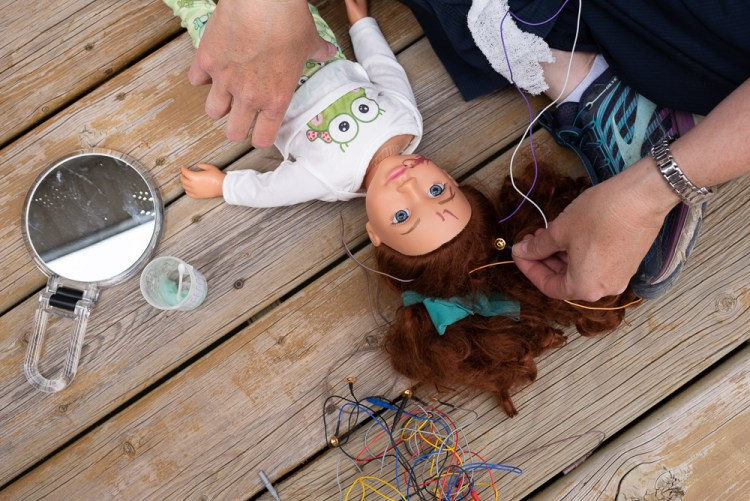 Prior to an EEG a family uses a doll to teach what the procedure will look like.