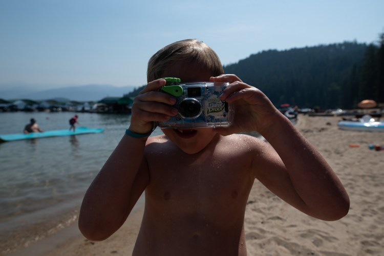 A child holds up an underwater camera at the beach.