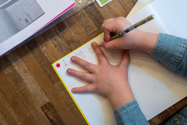 A young child uses their finger to space words when writing.