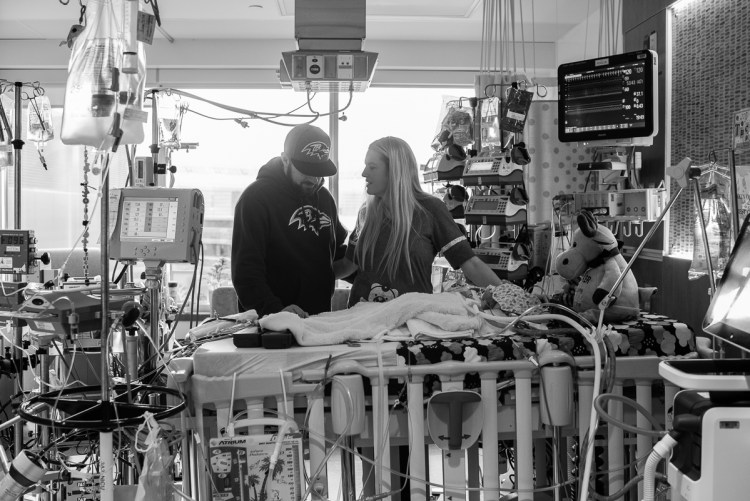 Parents spending time with their son in the Pediatric Cardiology Intensive Care Unit.