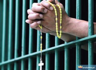 Więzień modli się na różańcu