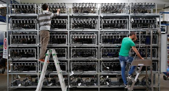 Employees work on bitcoin mining computers at a factory in Florence. Alessandro Bianchi / Reuters