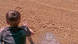 Handabdrücke eines Kindes im Getreide
