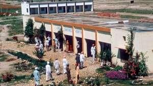 wartende Patienten vor Multifunktionsgebäude mit Arztpraxis