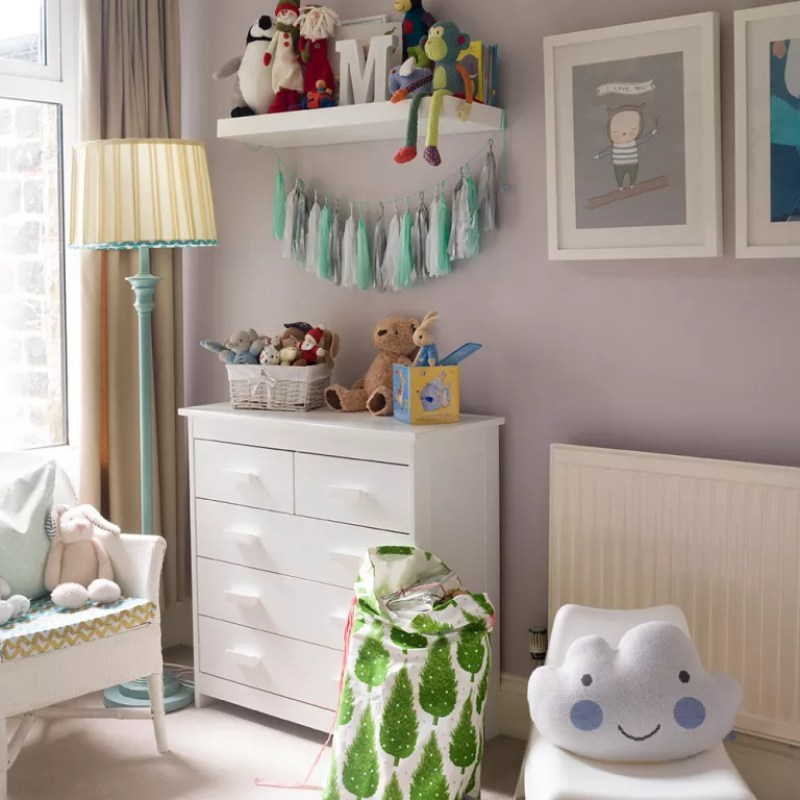 Grey nursery with white chest of drawers floor lamp and tassel bunting on shelves