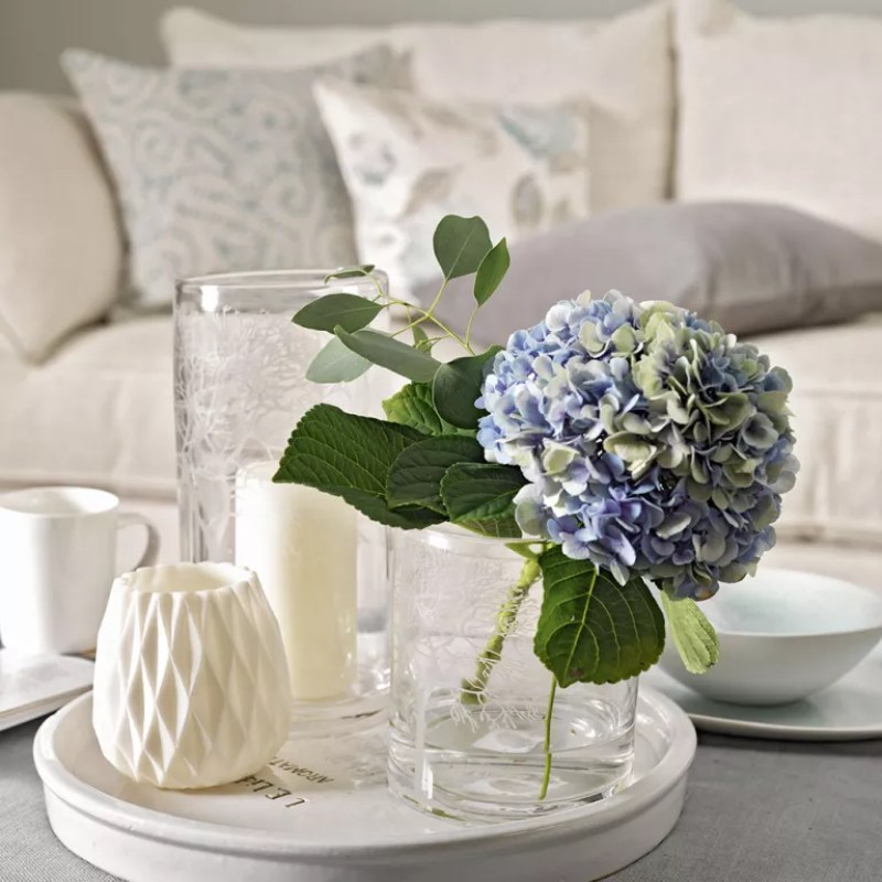 hydrangea flower in a small vase on a tray with ornaments
