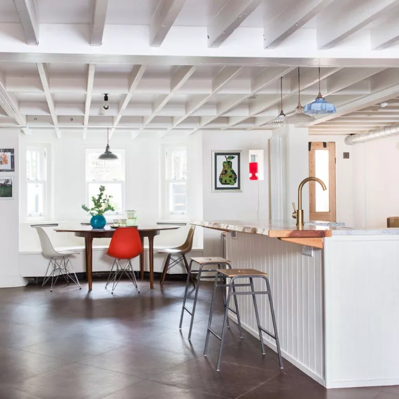 mismatched chairs in an open plan kitchen diner with kitchen island