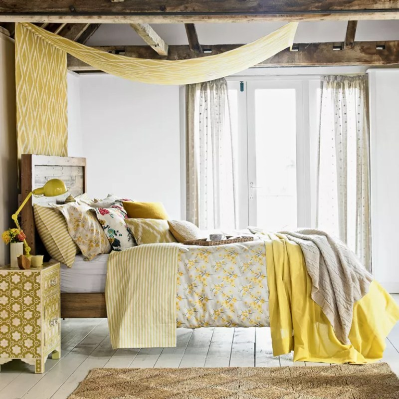 a bedroom with a bed dressed with yellow printed covers and ceiling hanging