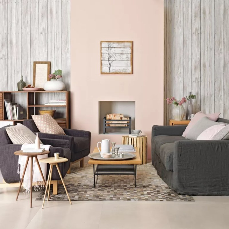 Living room with pale pink chimney breast wall with faux wood wallpaper in alcoves either side with dark grey sofas