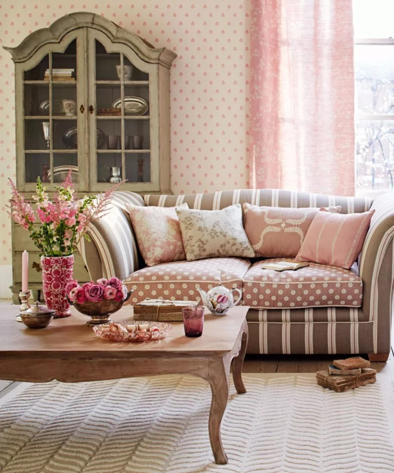Pink living room with taupe and beige stripe sofa and French armour display cabinet