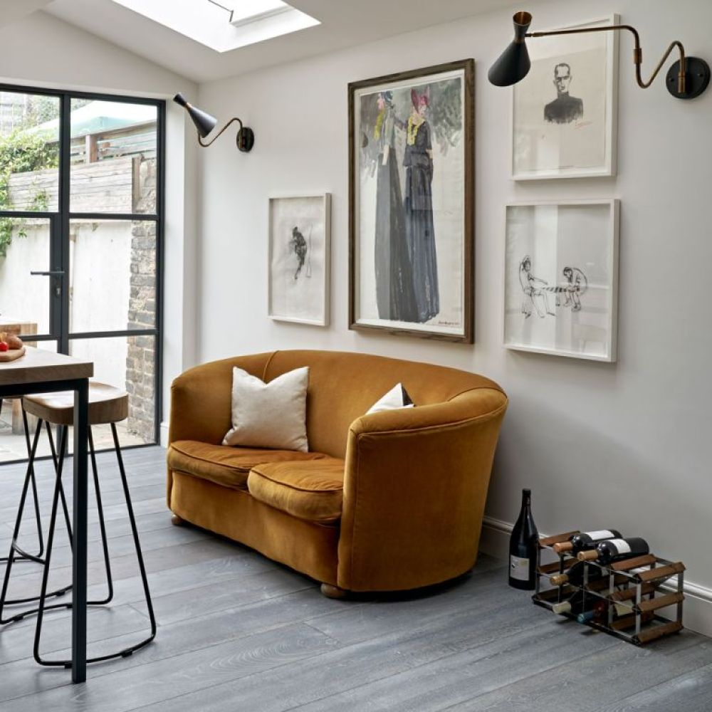 open-plan living room with wall lights over mustard velvet sofa