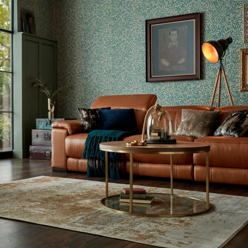 green living room with small leaf print wallpaper and brown leather sofa