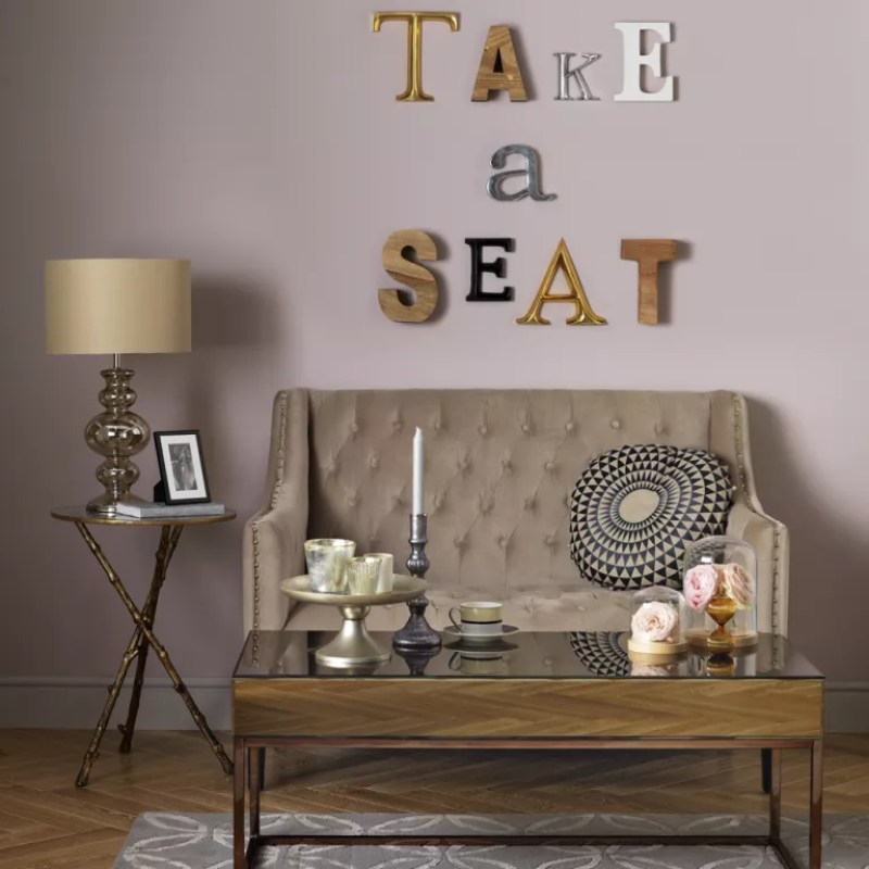 pink living room with small button back sofa wooden coffee table and wall-mounted letters artwork