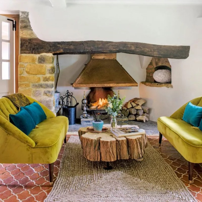 a cottage living room with acid yellow velvet sofas, natural tree trunk coffee table and restored fireplace