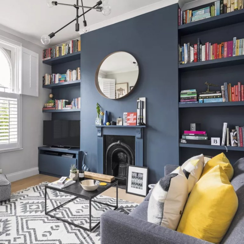 living room with navy feature wall with bookcases