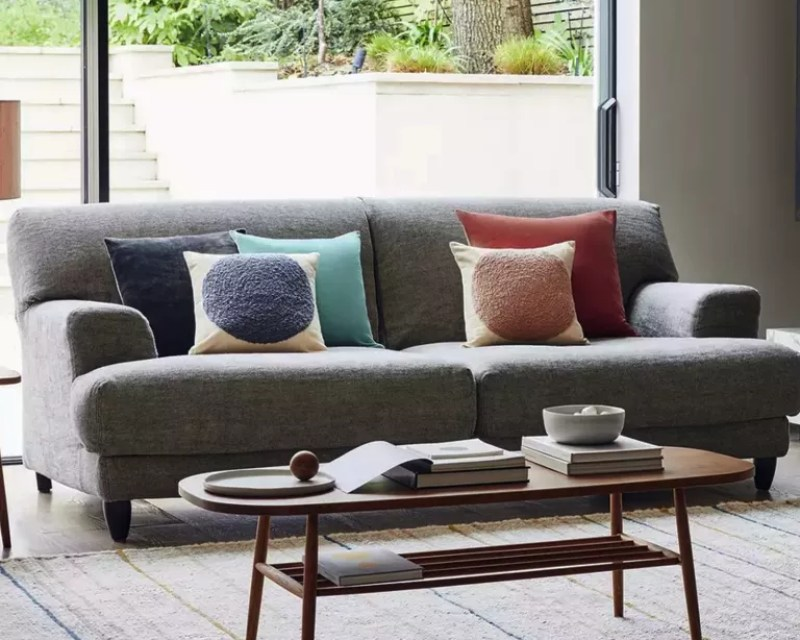 A grey sofa in a living room with a sliding glass door