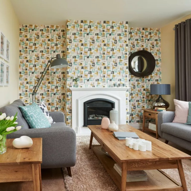 light yellow and grey living room with patterned wallpaper feature wall