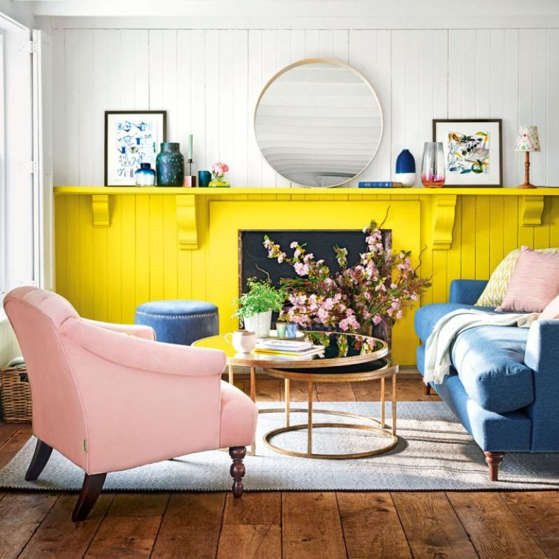 Pale grey living room with bright yellow painted wall and fireplace