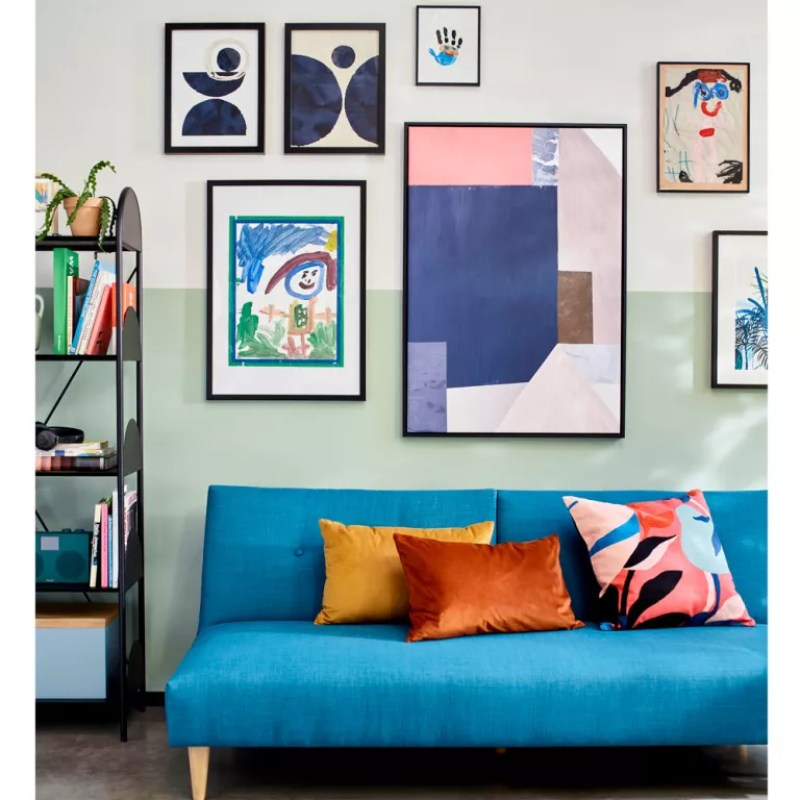 Living room with two tone green and white wall with gallery wall idea and blue sofa