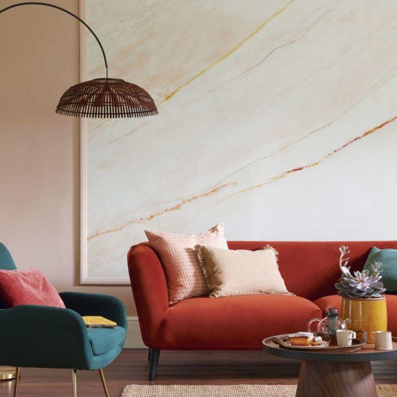 framed wallpaper artwork in living room behind orange velvet sofa