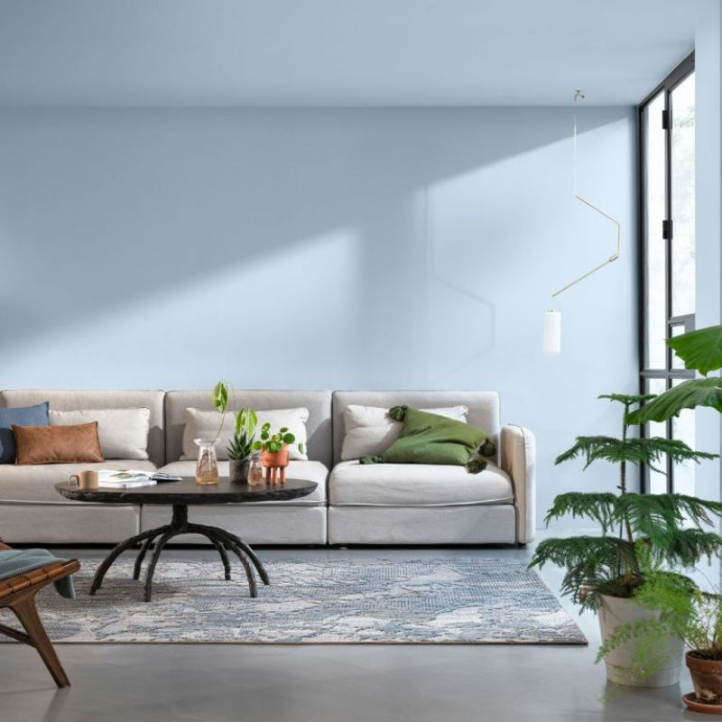 blue living room with neutral sofa and plants