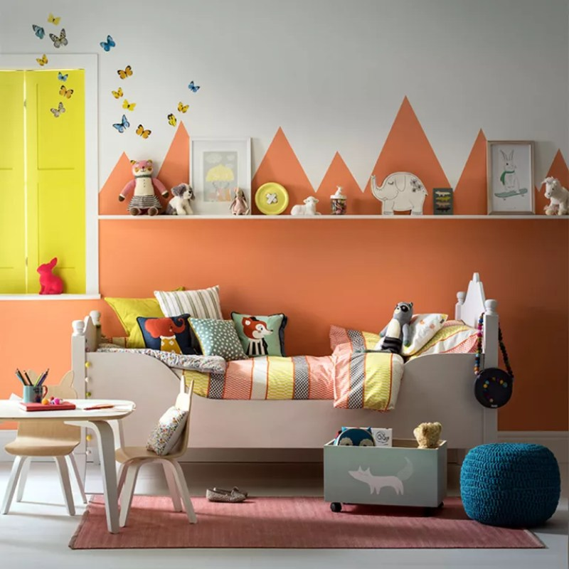 girls nursery with orange painted wall scape and cot bed