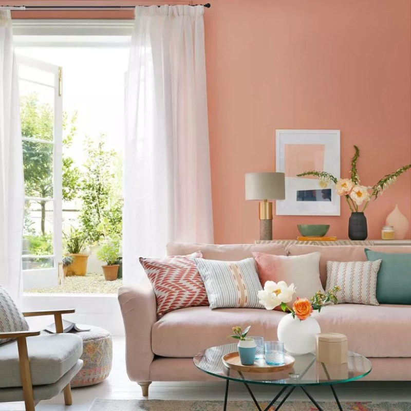 peach walls in a living room with sheer curtains and pink sofa - Dominic Blackmore