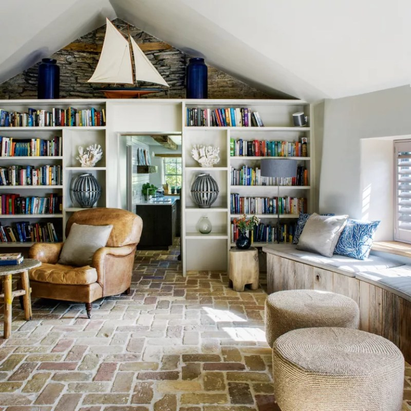 A country style cottage living room with exposed brick, bookcase and leather chair - Polly Eltes