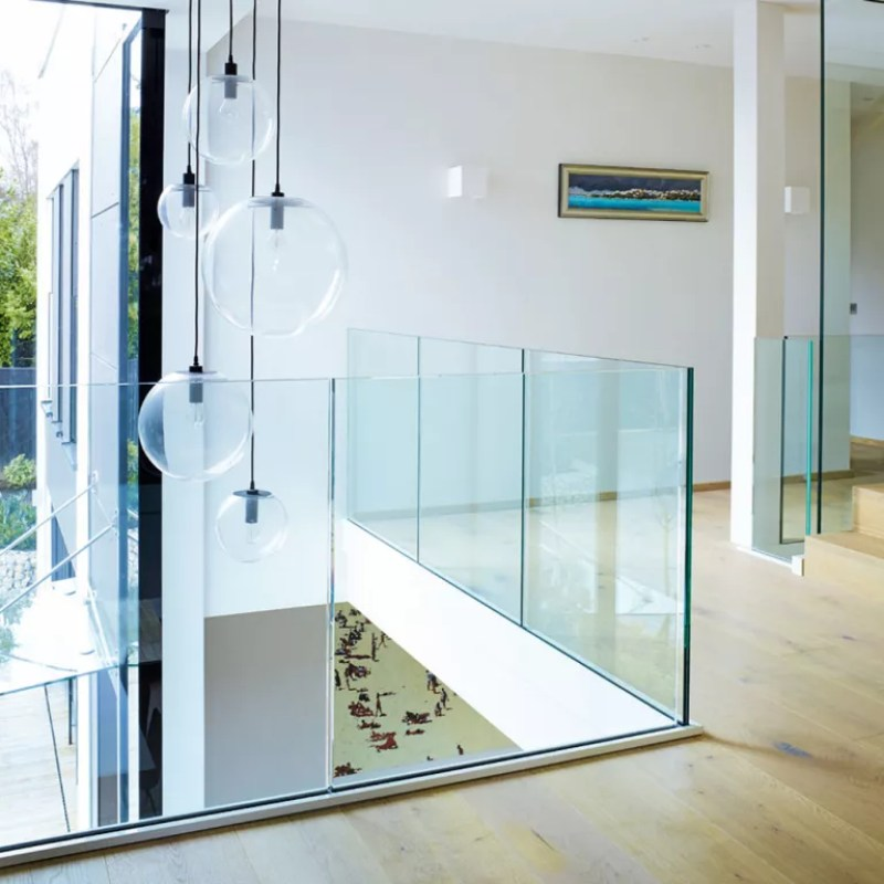 Upstiars landing with wooden flooring and glass stair panels
