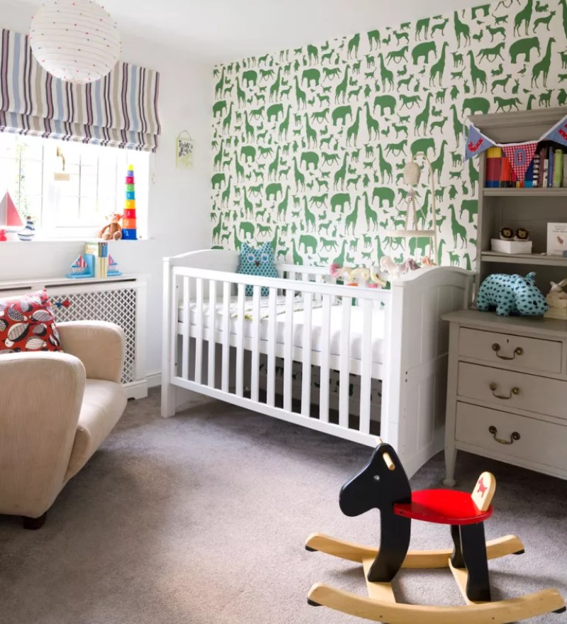 nursery with green zoo print wallpaper feature wall