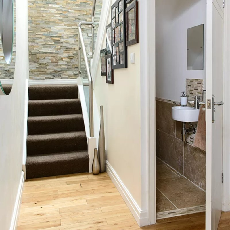 under stairs toilet stone wall tiles and brown carpet
