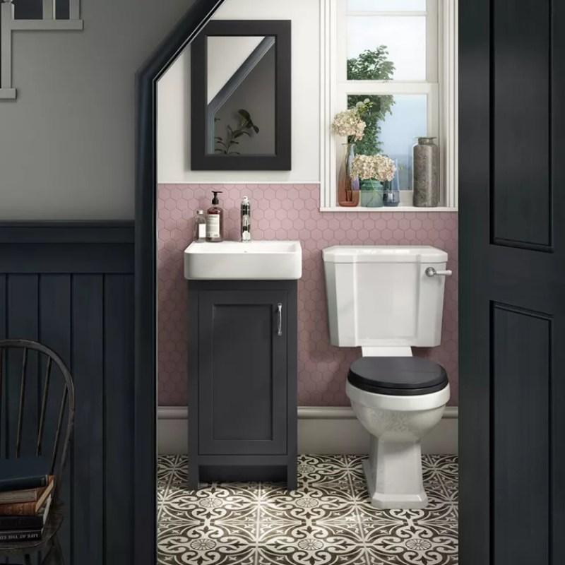 under stairs toilet with pink and white walls and black paintwork