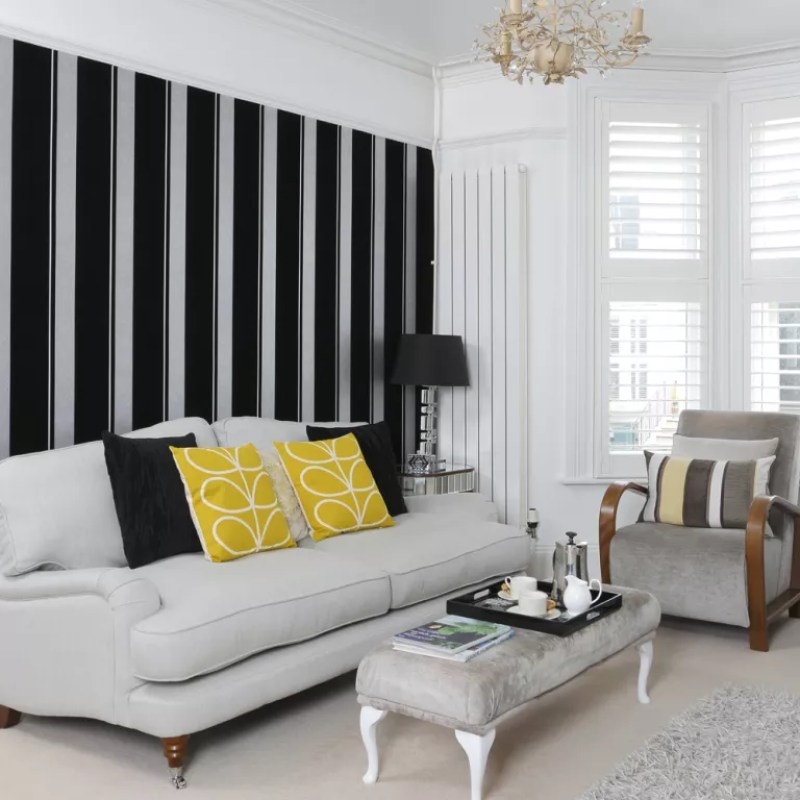 Black and silver striped wallpaper feature wall behind sofa in living room