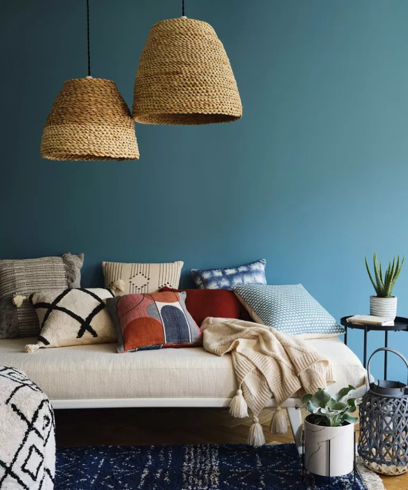 Two large rattan pendant lights hung over a day bed layered with cushions