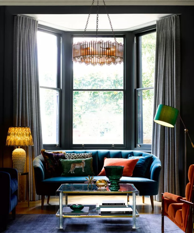Living room with large bay windows, blue sofa and statement chandelier
