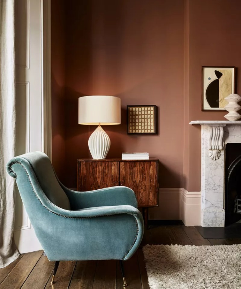 Blue armchair by sideboard with table lamp on top